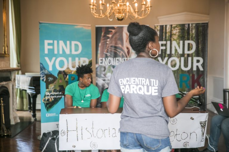 Historias de Boston participant stands in front of a table where the group interviewed other youth at the 2018