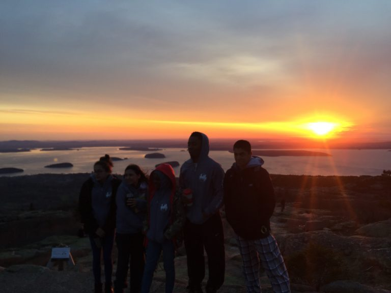 Group photo of Spring 2018 PLACE Fellows in front of a sunset at Acadia National Park
