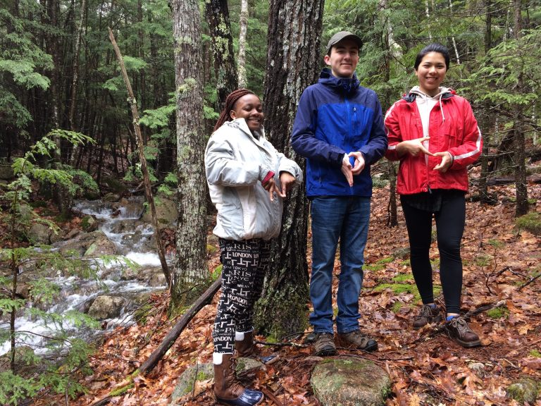 Photo of three Fall 2017 PLACE Fellows spelling NPS with their hands in Acadia National Park
