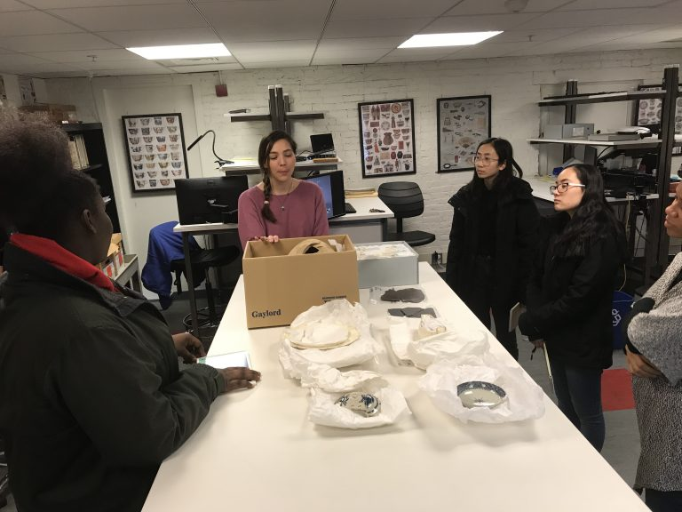 Photo of 2019 PLACE Fellows at a table with artifacts at the National Parks of Boston