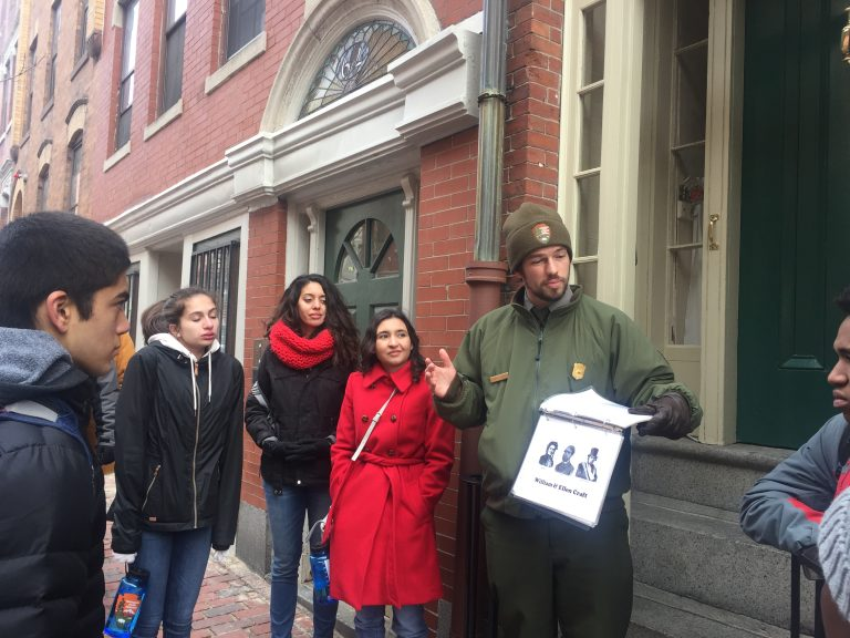 Photo of Spring 2018 PLACE Fellows and a program lead listening to a Ranger on the Black Heritage Trail