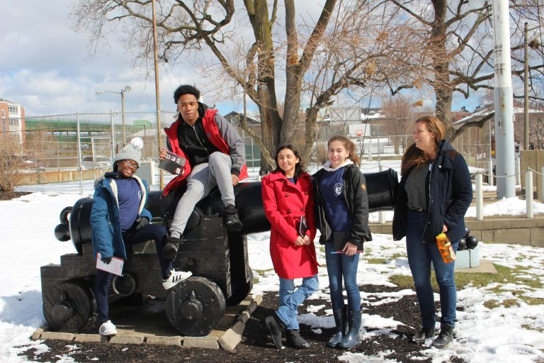 Spring 2018 PLACE Fellows and a program lead on and around a cannon at the Charlestown Navy Yard