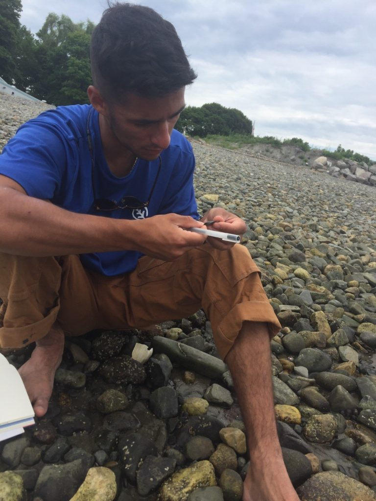 A Historic Preservation Fellow notes an object found on a rocky beach in the Boston Harbor