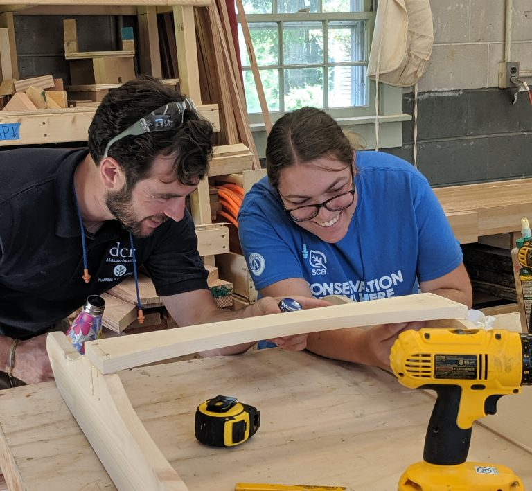 A DCR employee collaborates with a Historic Preservation Fellow on a maintenance project