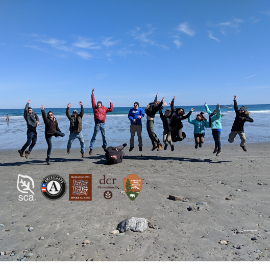 All but one Historic Preservation Fellows jump together on a beach