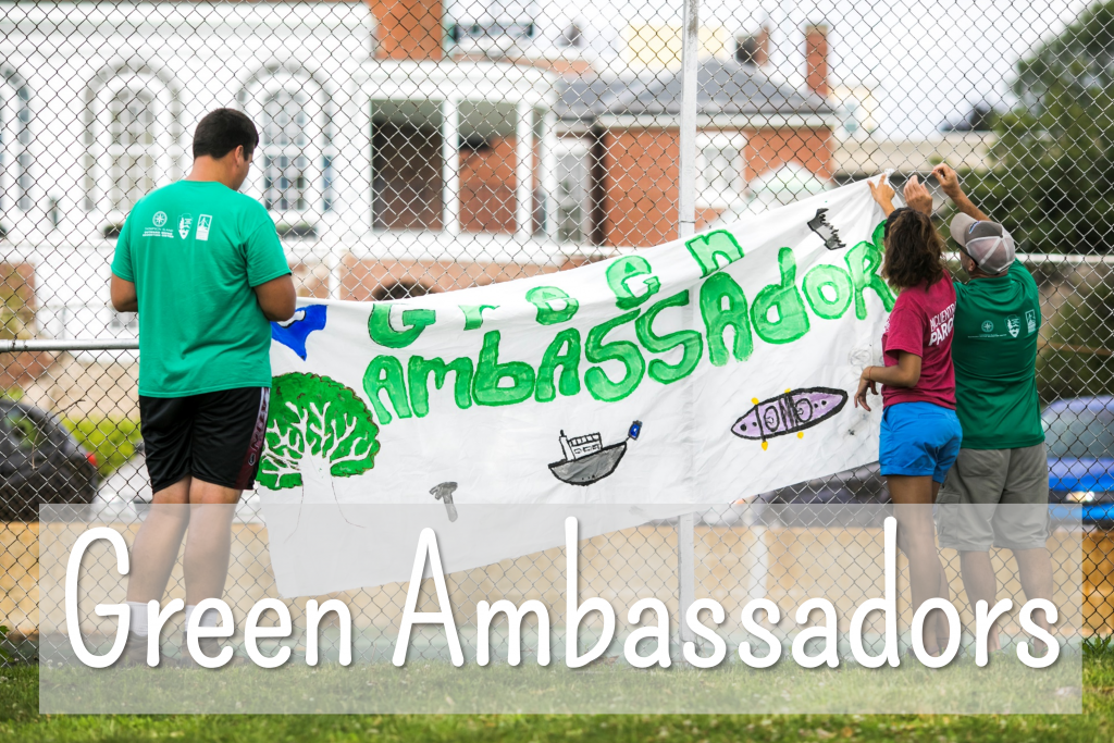 Green Ambassadors hang up a sign featuring their group name and decorated with a tree, a hammer, and boats