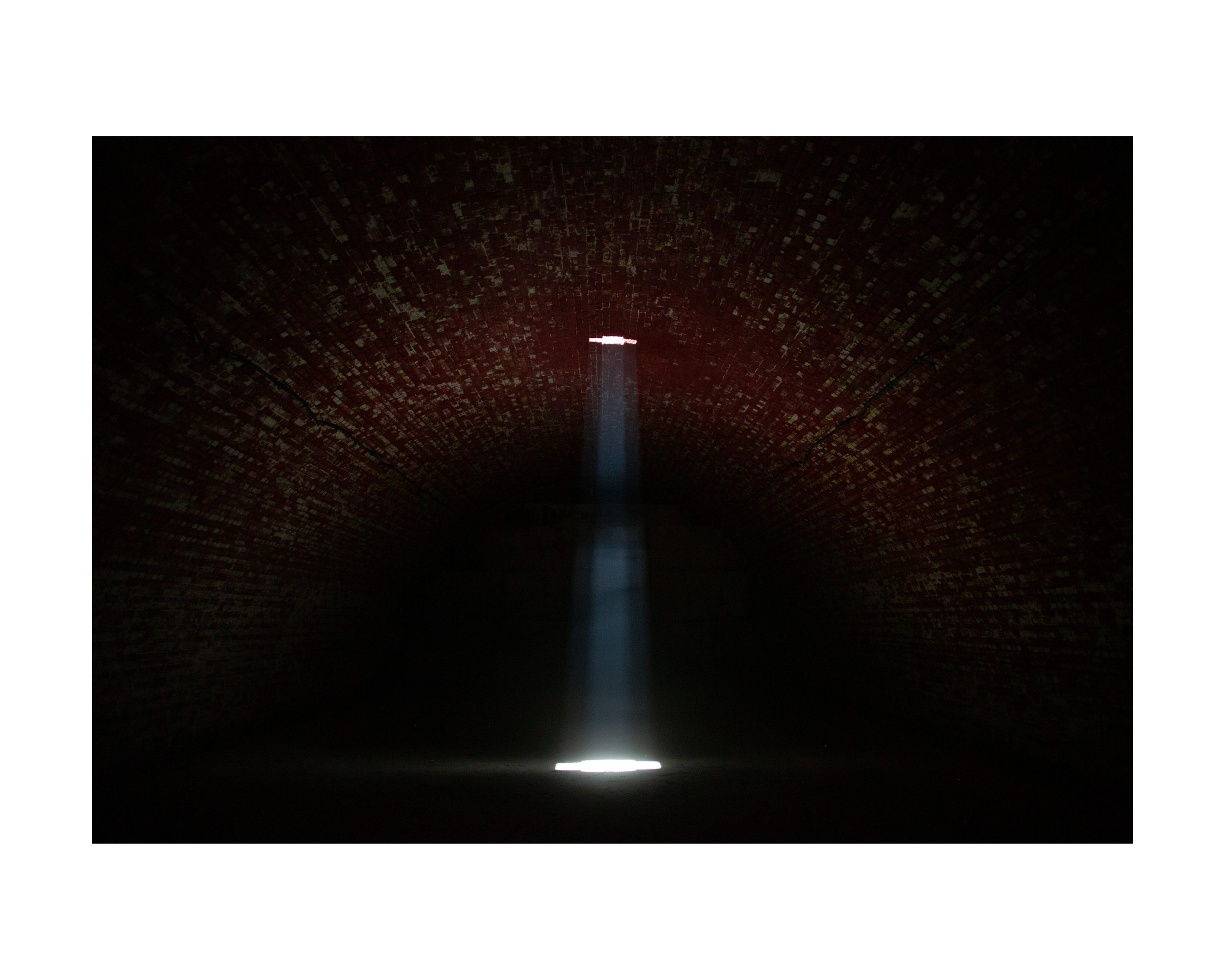 Single ray of light in the center of a dark cave-like room