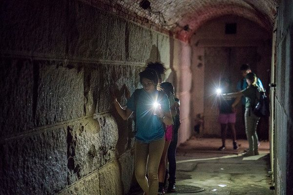 Photo of a 2019 Hill to Harbor YCC lead campers through a dark tunnel on Georges Island