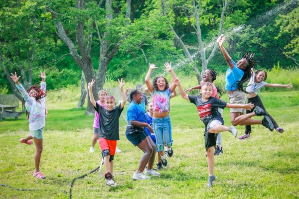 Photo of campers and a 2019 Hill to Harbor YCC jumping in spraying water on Peddocks Island