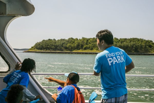 A Hill to Harbor Corps member stands with two campers on a ferry in the Boston Harbor