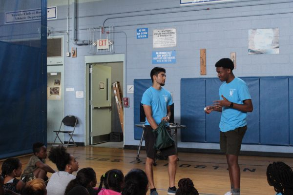 Photo of two 2019 Hill to Harbor YCCs presenting in front of campers at a pre-visit