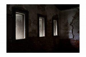 three windows in a dark wall