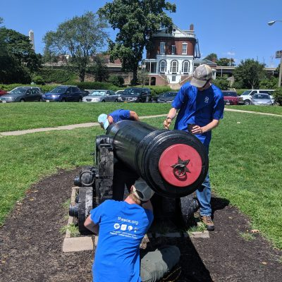 Historic Preservation Fellows work on a cannon in the Navy Yard