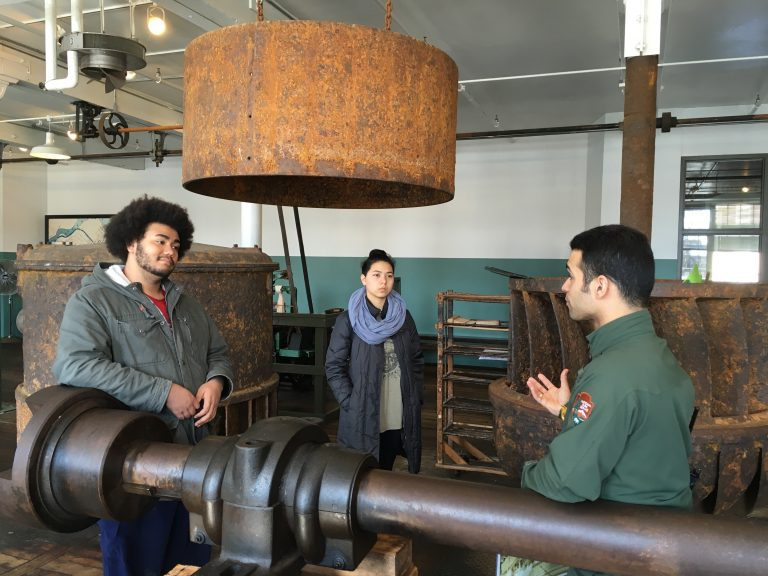 Photo of two Fall 2017 PLACE Fellows listening to Ranger Victor at the mills at Lowell National Historic Site